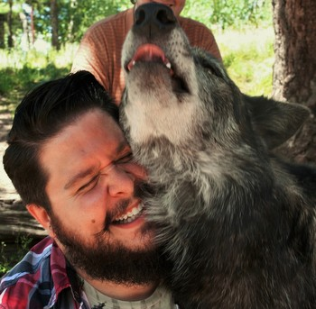 John Whatley with a friendly wolf at the Colorado Wolf and Wildlife Center.