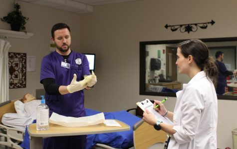 ACC nursing student Ross Fraser demonstrates how to correctly apply sterile gloves as instructor Stephanie Armstrong observes on Feb. 10, 2018, in Littleton, Colo. ACC and other community colleges could offer bachelor's degrees in nursing if House Bill 1086 becomes law.