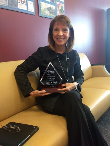 A cheerful Dr. Doyle showcases her Presidential Excellence Award.