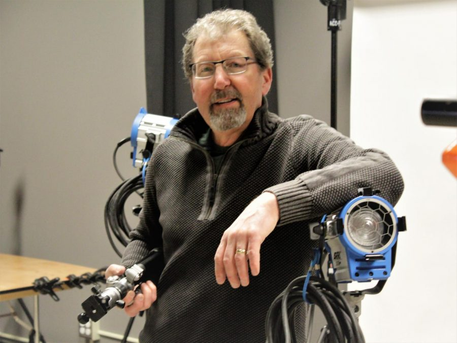 Brad Bartholomew, head of the photography department, posing with the lighting equipment, holding a tripod in the Arapahoe Community College Art and Design photography building on Feb. 19th 2019.