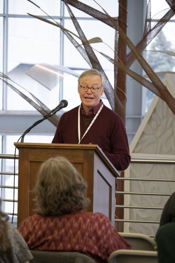 ACC Writes, Mark Kelly was a featured writer who read a piece he wrote, Wednesday, Feb 27, 2019. Featuring author Jane Binns, sits in audience listened to fellow writer lover speak about the background of his writing piece.