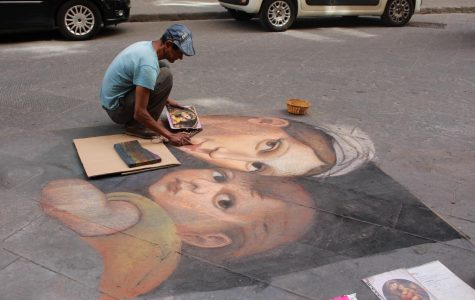 A chalk artists makes a traditional painting out of chalk on a side street in Florence, Italy. Photo taken on Saturday June 15, 2019.
