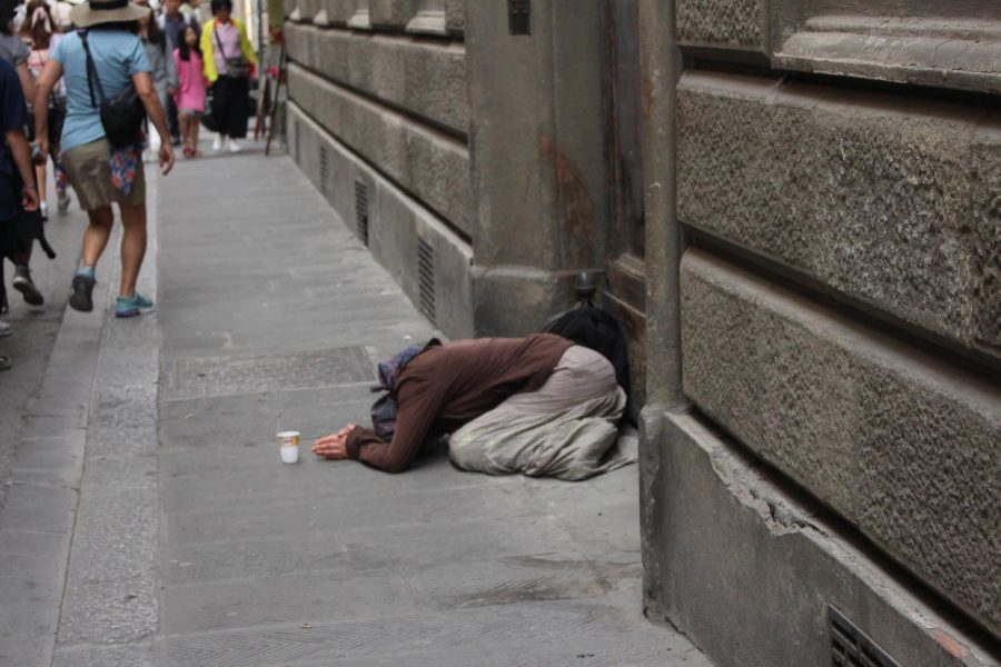 A woman lays on the ground with a cup for change outside of the Galleria Academia in Florence, Italy. Photo taken on Saturday, June 15, 2019.