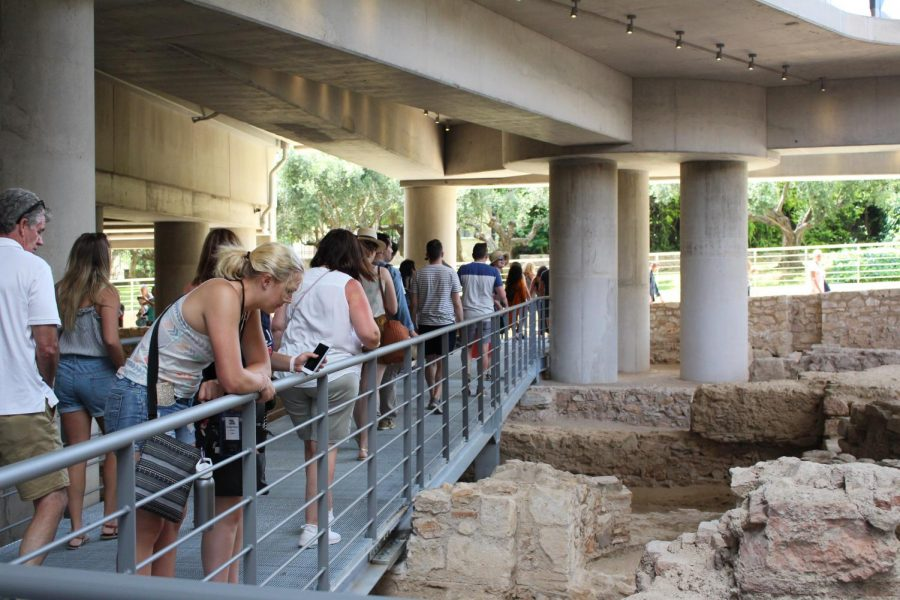 Groups of people walk around the ruins.  The railing protects both the visitors and the excavation site. Photo taken on Monday, June 24, 2019.
