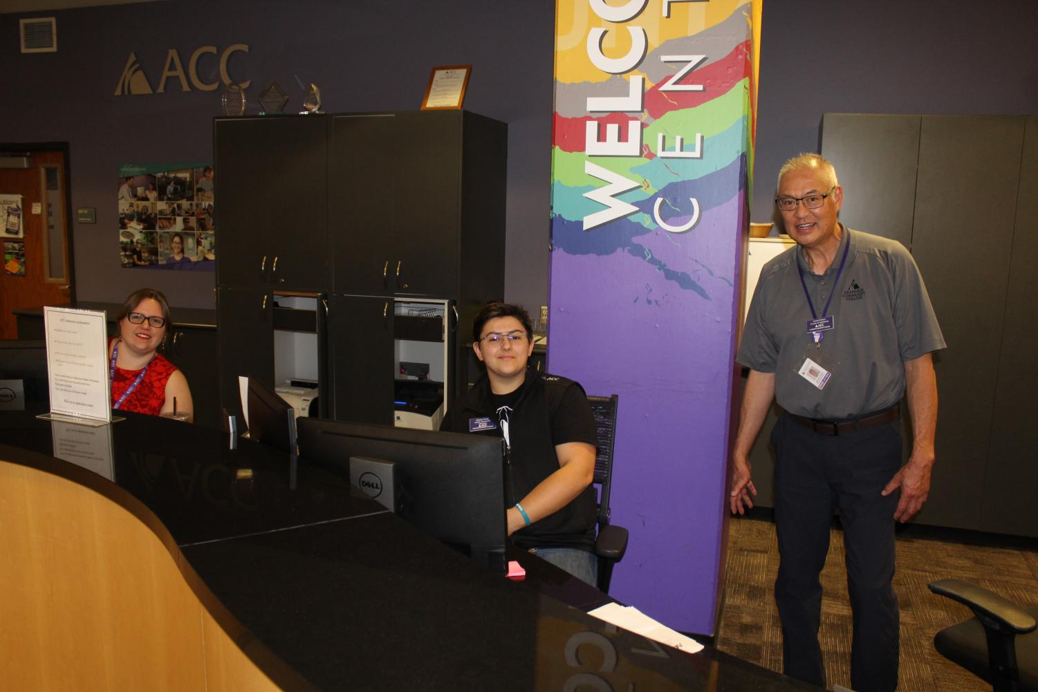 Jennifer Sheldon (left) and Charles Frank (middle) and Howard Fukaye (right, not featured in this article) working behind the ACC Welcome Center Desk in the midst of their many daily duties. Image via Jaymes Grundmann