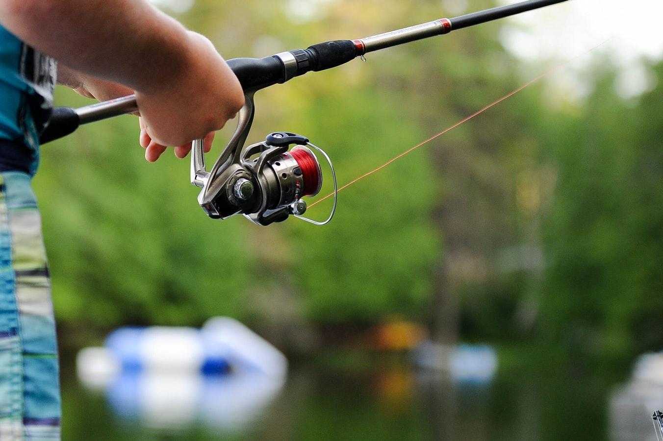Man holds fishing rod. (via unsplash.com)