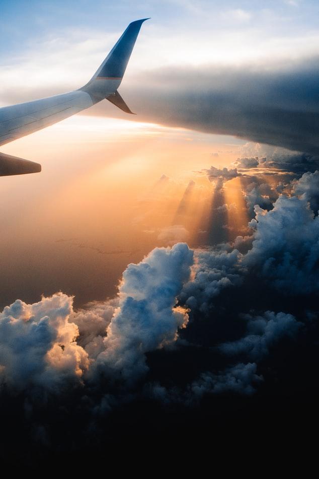 Wing of an airplane in sunset. (Image via Unsplash/Tom Barrett)
