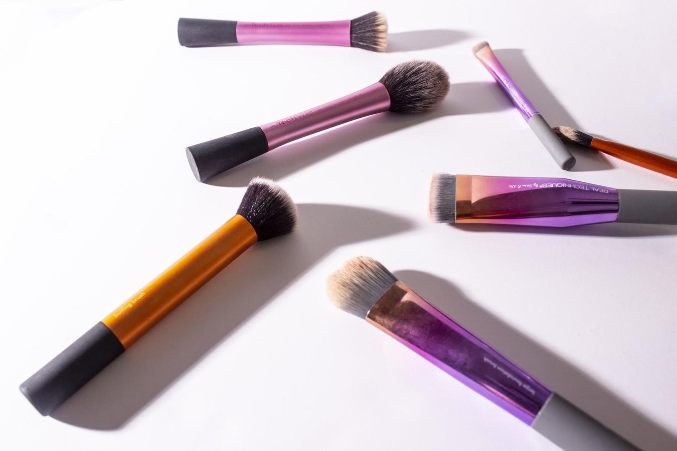 Assorted-color makeup brushes on white surface. (Photo via Unsplash,com/GlowRepose)