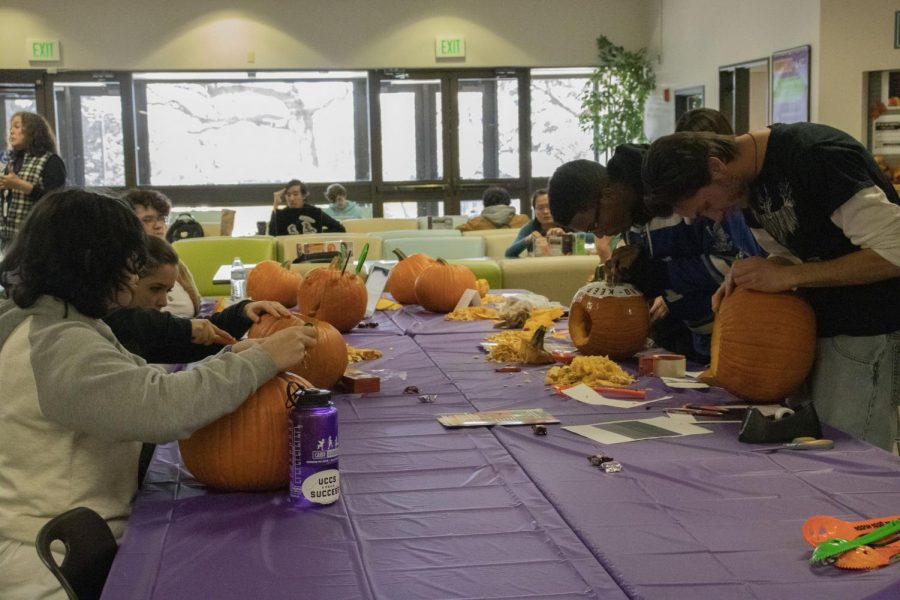 ACC students carving out their designs for the pumpkin carving contest in the student lounge on Thursday, October 24, 2019.