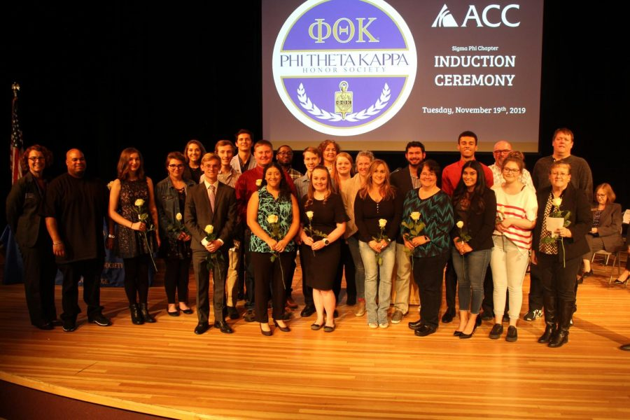 Phi Theta Kappa members and Arapahoe Community College faculty  pose on stage at the end of the PTK Induction Ceremony at Arapahoe Community College in Littleton, Colo., on Tuesday, Nov. 19, 2019.