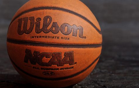 NCAA basketball on black pavement. (Photo via Unsplash/Ben Hershey)