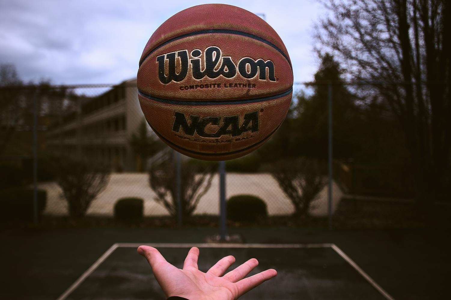 Hand tossing an NCAA basketball into the air at an outside court. Image via Dan Carlson, Unsplash.