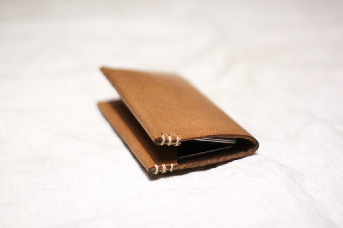 A flat wallet laying on a white counter top. the slightly open face of the wallet signifies it's content are that of value.
