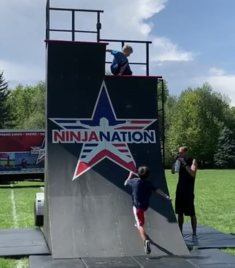 Owyn Lee Atop the Ninja Nation warped wall on Sept. 8, 2019. Lee having just conquered the warped wall is quickly followed by another child.