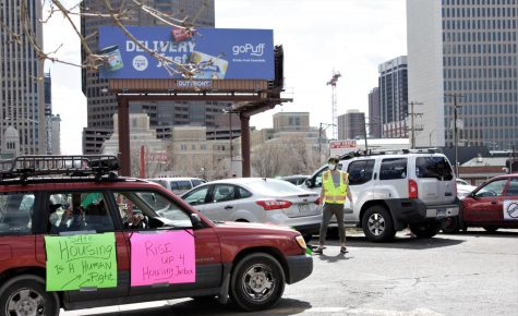 A car with a sign taped to the outside stating drives into the parking lot to prepare for Cancel The Rent Housing 4 All car protest during COVID-19 on April 25 2020 in Denver.