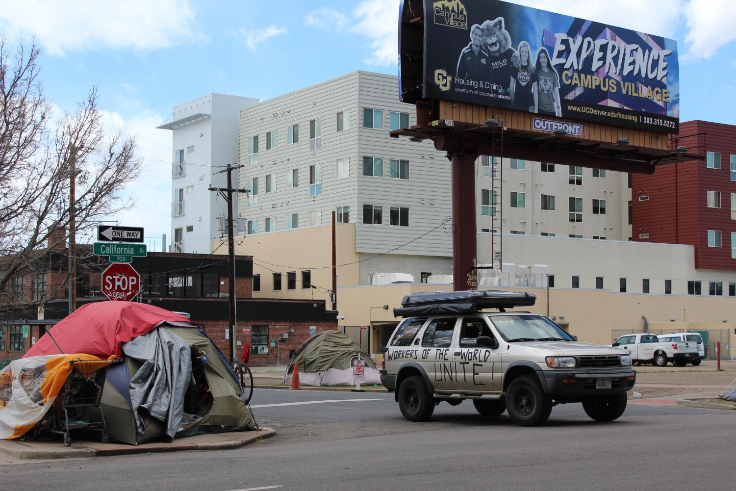 "A car with the words ""workers of the world unite"" drives past a tent on California St on April 25, 2020."