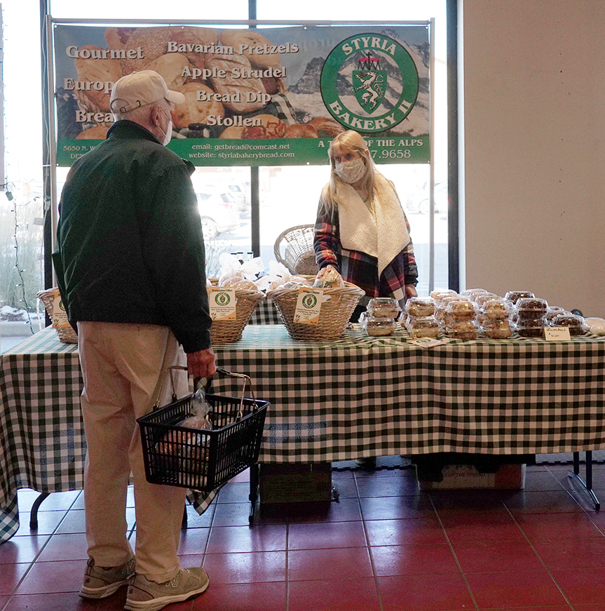 Shannon Campbell, owner of Styria Bakery II, talking with customer at Christmas in the Rockies Gift Mart, Aspen Grove Shopping Center, December 4, 2020.