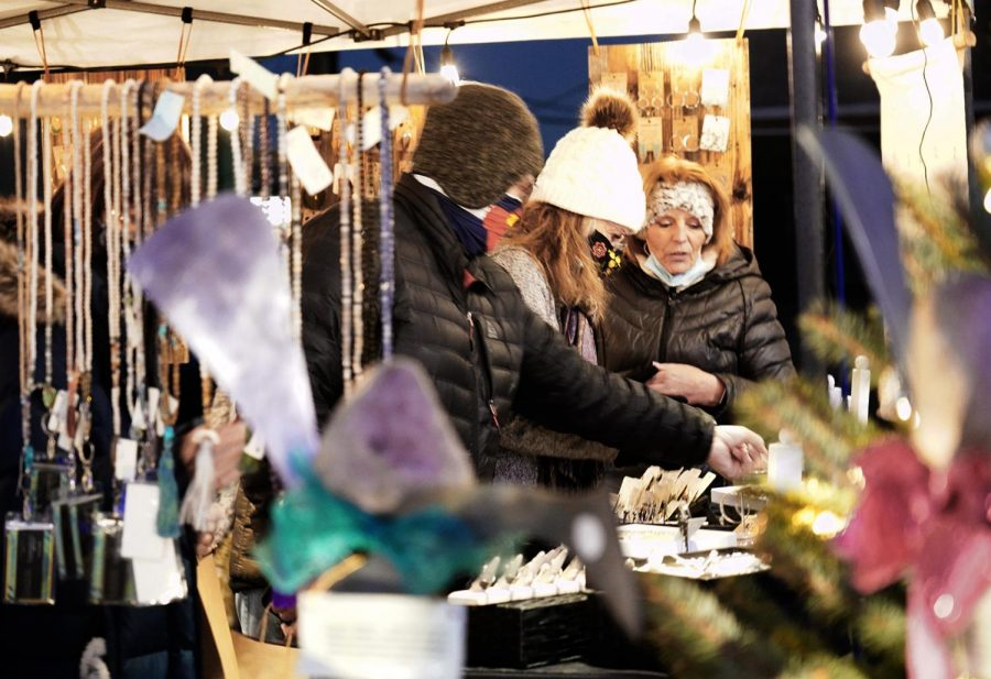 (Right) Cynthia Kennedy, owner of Two Gems Boutique answers shoppers questions about her handcrafted jewelry. Festival Park Starlight Market, Friday, Dec., 4, 2020.