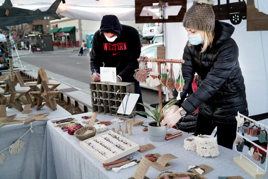 Idyllwild Designs Co, owners, Nedra and Dustin Smith work to keep things organized during Festival Park Starlight Market. Dec. 5, 2020.