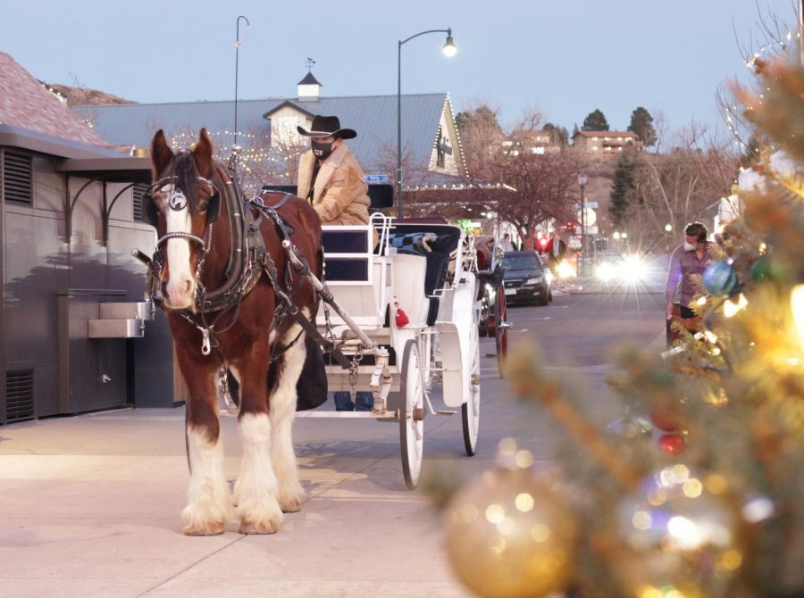 Horse-drawn carriage at the entrance of the Festival Park Starlight Market, Castle Rock, Colo., Dec., 5, 2020