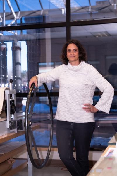 Angela Faris Belt Program Chair posing by the schools Print & Press Machine for ACC's AFA degree development.