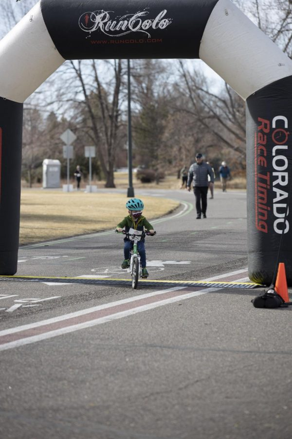 Child on a bike crosses the finish line at the 5K Polar Plunge, Sunday March 7, 2021.