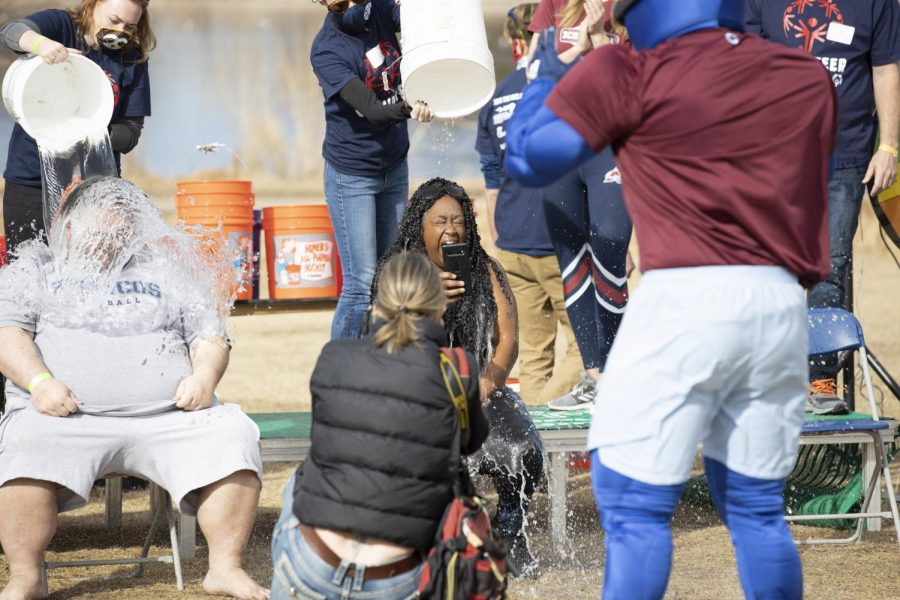 A participant gets photographed while getting splashed with cold water at the 5k polar plunge. Sunday March 7, 2021