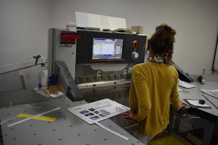 Abby Noble demonstrates the industrial paper cutter used to cut sheets down to size on April 23, 2021.