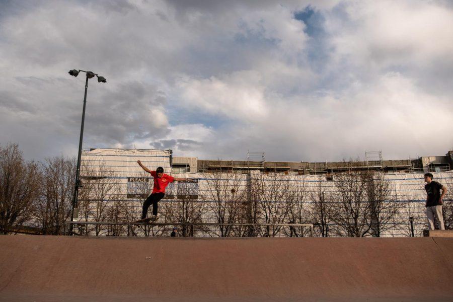 Skateboarder performing a grind on a rail at the Downtown Denver Skatepark.